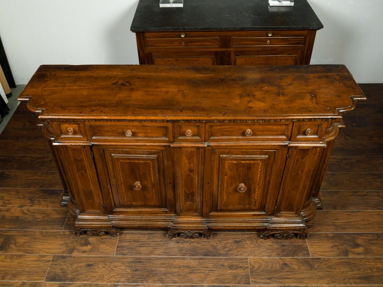 An Italian walnut credenza from the early 19th century, with drawers over doors, inlay and carved feet. Created in Italy in the early years of the 19th century, this walnut credenza features a rectangular top with rounded corners in the front,
