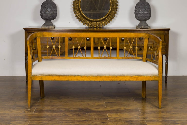 An Italian walnut settee from the early 19th century, with X motifs, gilded medallions and new upholstery. Born in Italy during the first quarter of the 19th century, this walnut settee features a pierced back, accented with X motifs and gilded