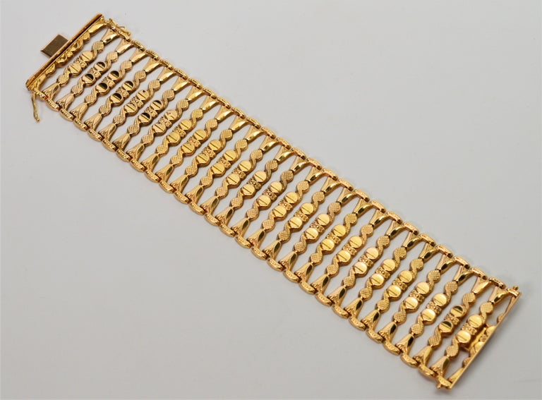 Distinctive, this striking eighteen carat yellow bracelet is sure to be a prominent piece in your jewelry wardrobe. This hand made Italian 1950's  ladder link bracelet measures a substantial 1-3/4 inches wide.  Twenty seven flexible decorative