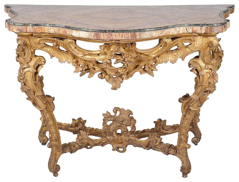 A good quality 18th century Italian carved giltwood console table, having a quarter veneered marble top, carved scrolling foliate decoration, raised on carved cabriole legs that are united by a carved X-stretcher.