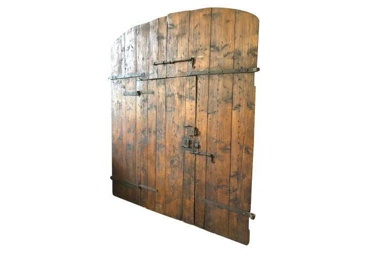 Tremendous 18th century entry doors from the Tuscan region of Italy. Soundly constructed from hard pine with excellent iron fittings. Beautiful from both sides. Great patina.