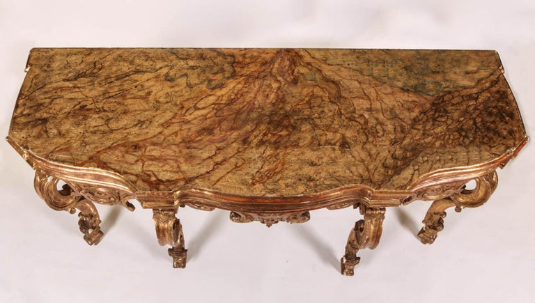 Elegant Nord Italian 18th century carved and giltwood console table with a painted faux marble top.