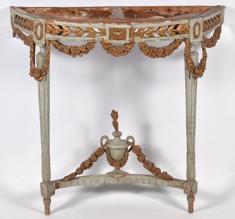 This wonderful Italian carved console table dates to the late 18th century and is fashioned in the French Louis XVI style of the period with openwork gilt wood frieze and carved garlands surmounting two circular reeded and tapering legs united by a