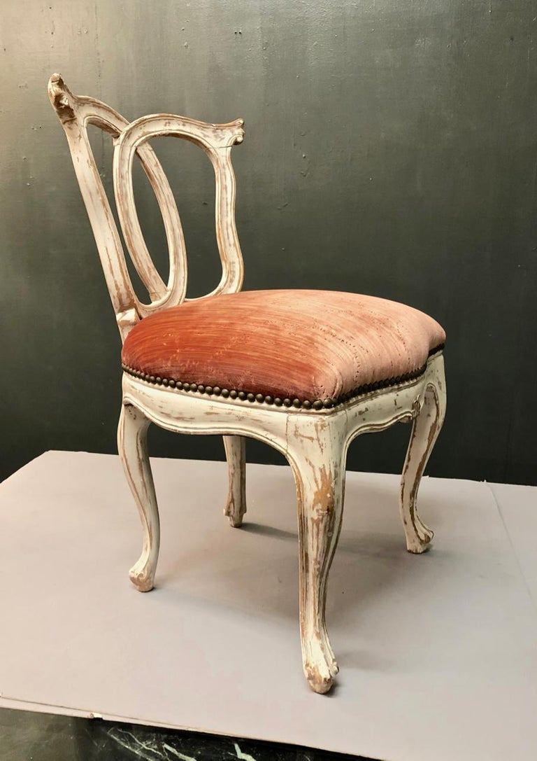 This a very sweet 18th century Italian slipper chair. The carved frame is in good condition and retains its original chalk-white surface; it has been newly upholstered in a high-end Italian silk velvet.