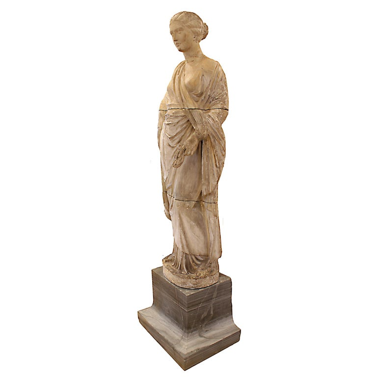 A monumental Italian 18th century terracotta statue. This large scale terracotta statue has a white glaze and is raised on a dark gray marble base. The statue is of a lady in classical draped attire with her hair upswept into a chignon. The statue