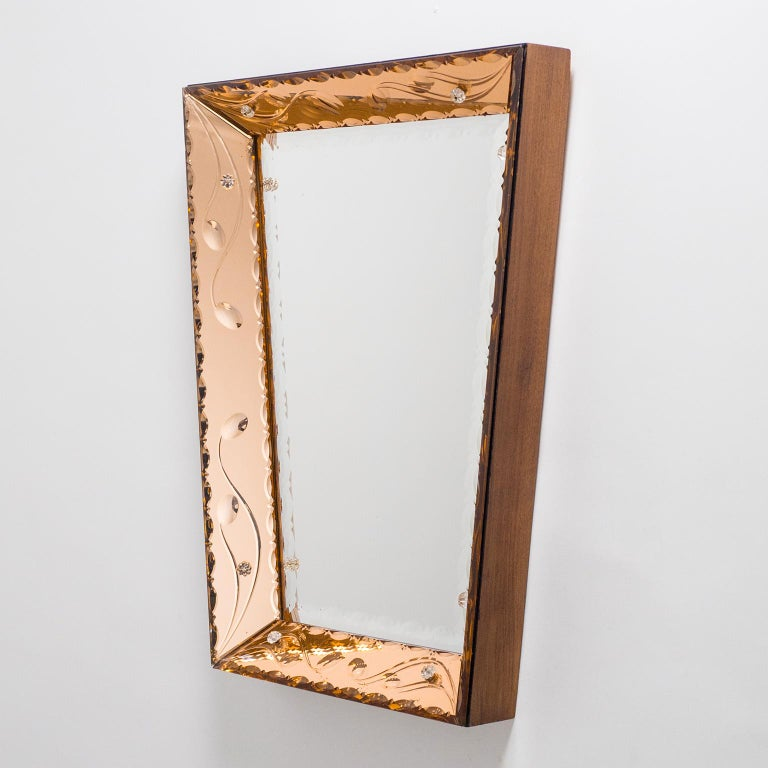 Beautiful Italian trapeze mirror with dual color mirrors. Inserted into a deep wooden frame are sheets of cut crystal glass in a copper or rose color as well as a clear mirror. Each of these are intricately beveled, scalopped and cut with abstracted