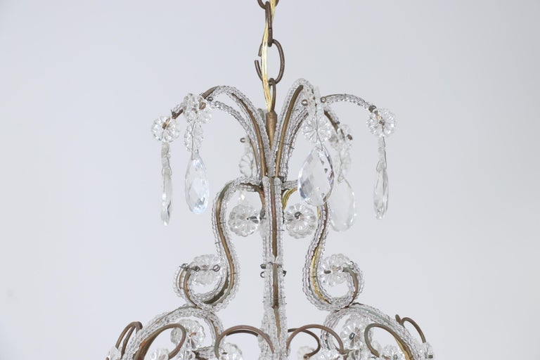 Beautiful, 1940s Italian gilt-iron and crystal beaded chandelier.  This chandelier consists of a scrolled gilded iron frame outlined with glass beads throughout its entirety and decorated with faceted crystal prisms. The iron frame has acquired a