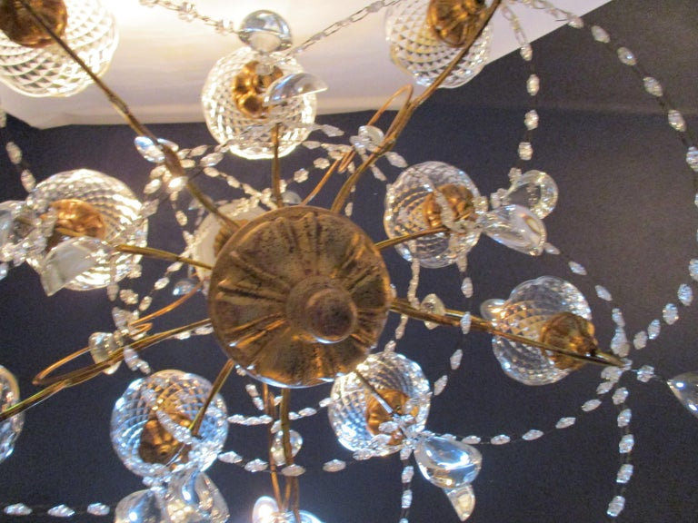 1940s Italian neoclassical ten-light giltwood pear crystal chandelier. Ten swoop arms with gilded armature and lined in Italian glass beads, stem outward from the lower portion of the central column, decorated with various crystals. Each arm