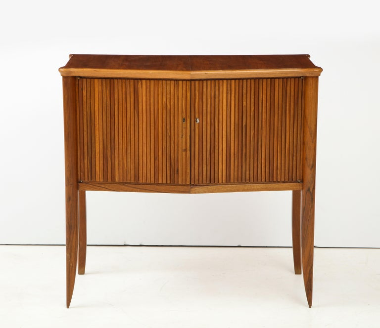 An Italian walnut two-door cabinet with ribbed carving, supported on elegantly tapered legs, the interior fitted with one shelf. Italy, circa 1940 Size: 39 1/2