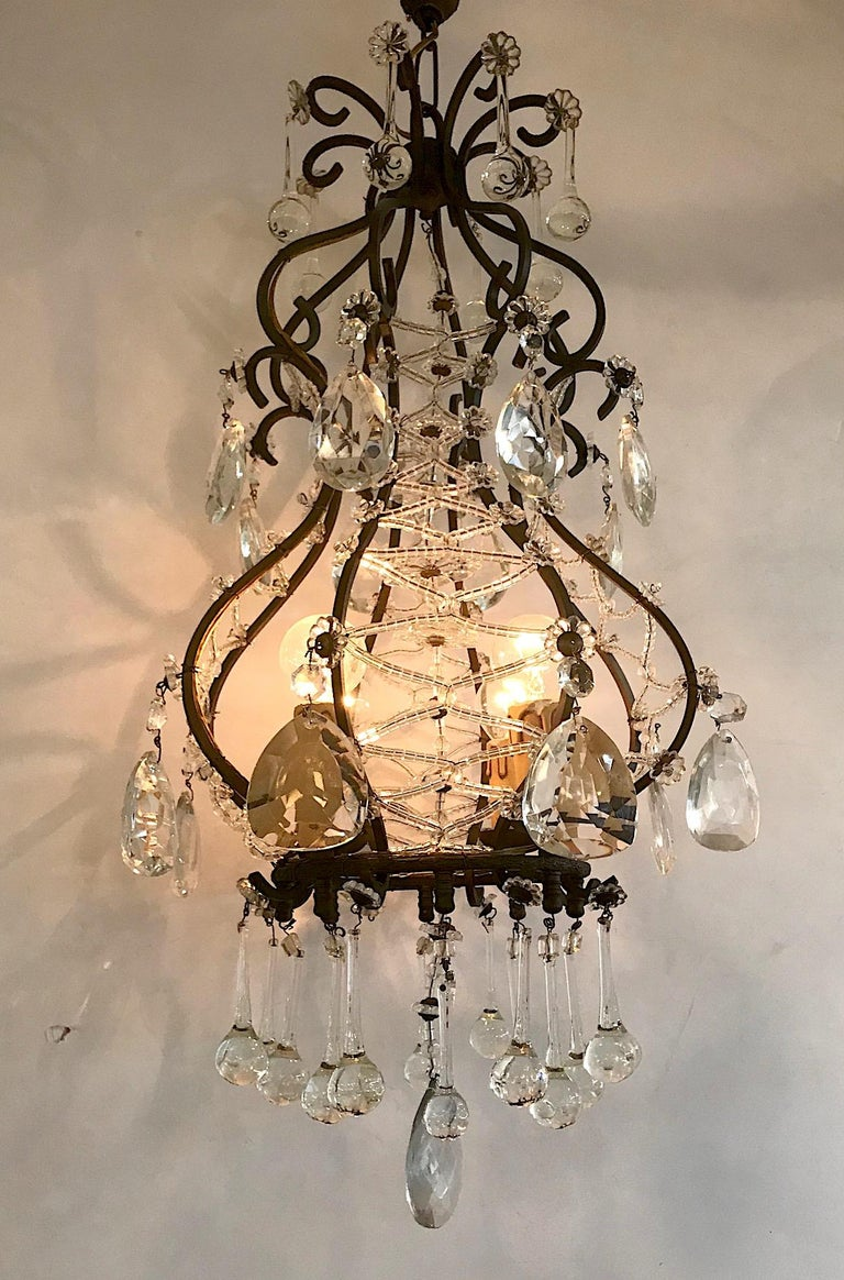 A stylish and charming 1950s Italian chandelier in patinated black iron with crystal and glass accents. The chandelier is comprised of 8 vertical scrolled iron supports. Four pair are wired in a criss cross pattern with handmade glass beads allowing