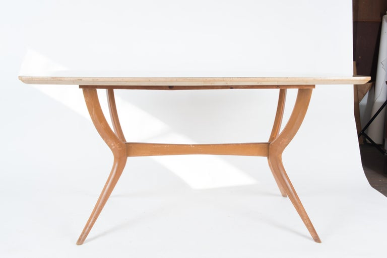 Sleek light wood 1950s dining table or desk. The wood top is hand painted under glass.