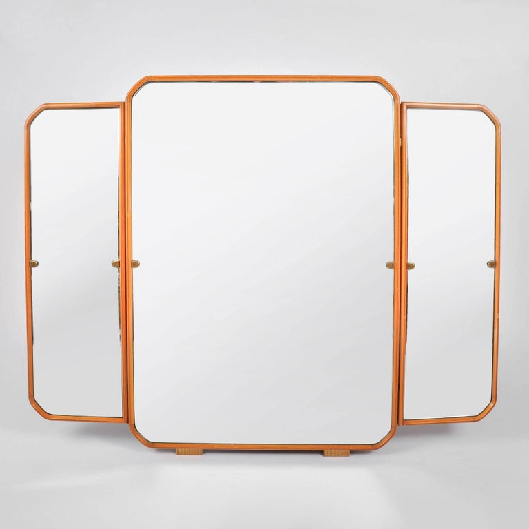 Substantial triptych wall hanging mirror. Pale fruitwood frame with curved corner detail. Decorative brass hinges and feet. The measurements below are for the whole mirror including the side panels – the central panel is 29.25 inches wide.