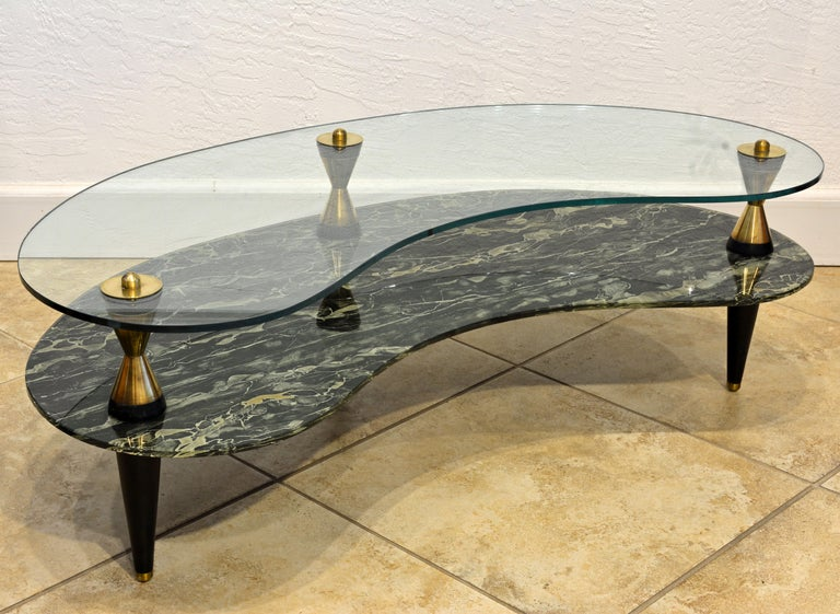 This typical midcentury sofa table features two kidney shape tiers, the top tier of clear tempered glass and the lower tier of tempered 'verre Églomisé' meaning painted on the back side. The legs are made with ebonized wood and solid brass cones and