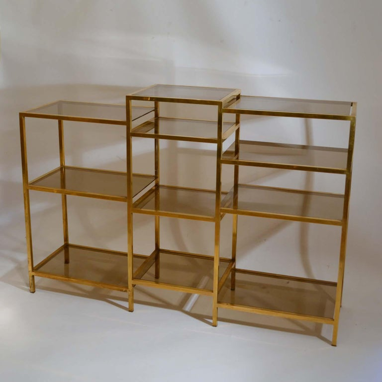 Freestanding multi-leveled brass étagère is divided in three sections of 3 to 4 shelves each at different levels, which varies from (96-106 to 108.5cm) with lightly tinted glass insets. Produced in the 1970s, the Italian company Romeo Rega started