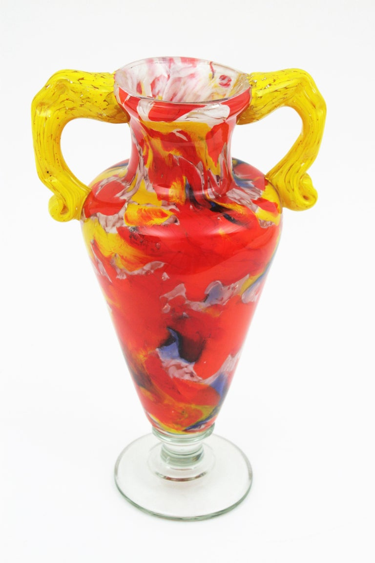 Amazing hand blown Murano glass vase with a colorful murrine glass decoration. A highly decorative piece in a vibrant red color, yellow handles and blue, orange and white accents, Italy, 1960s.