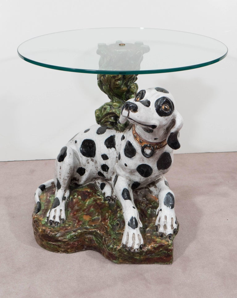 Occasional side table, produced in Italy circa 1960s, with round glass top, supported by a hand painted, faux bois ceramic base, designed as a twisted branch with leafy foliage, emerging from a mossy patch of earth, including a sweet dalmatian dog,
