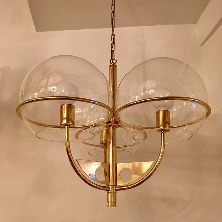 A 1970s swooping golden brass Italian chandelier with three large glass globe shades. Newly rewired.