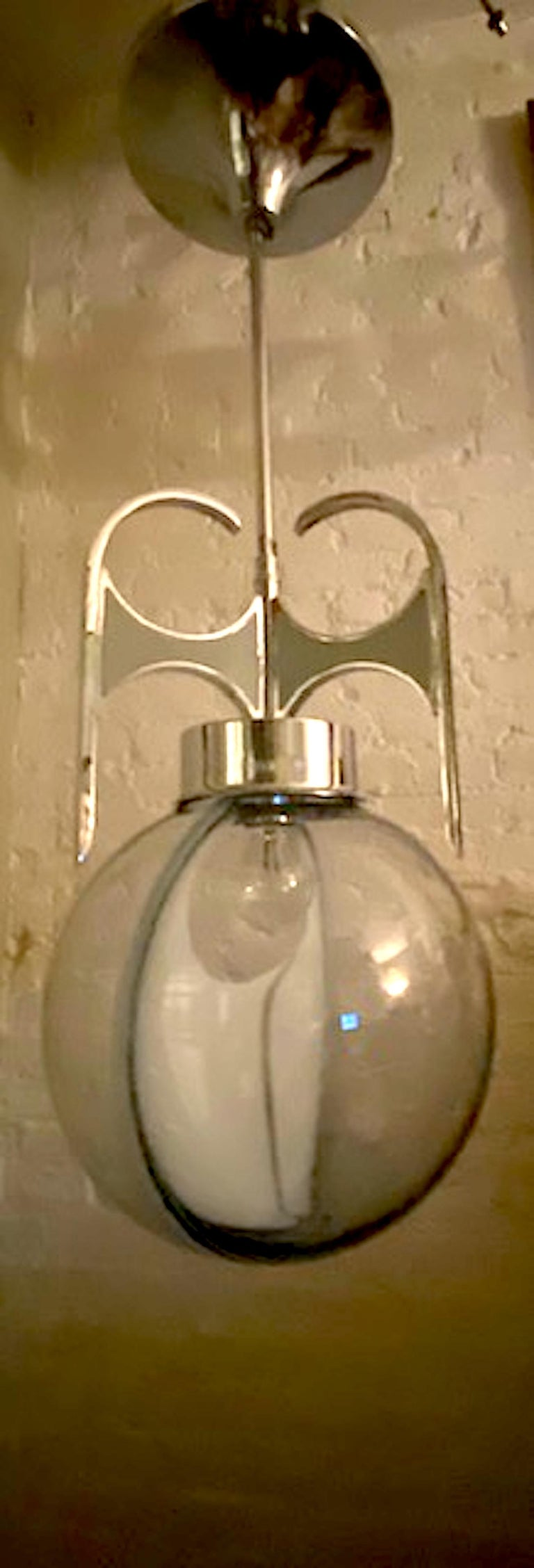 A wonderfully sculptural Italian pendant light from the 1970s in the style of the Italian lighting company Vistosi. The hand blown glass shade is clear with a light blue/grey tint. It has a decorative white glass crescent shape piece in the middle.