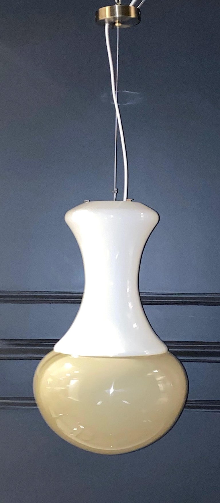 A clean and elegant design Italian Pendant light, circa 1970. The pendant is comprised of two pieces of hand blown glass made on Murano. The top is opaque white glass and the bottom is opaque taupe/beige color glass. The two pieces are glued