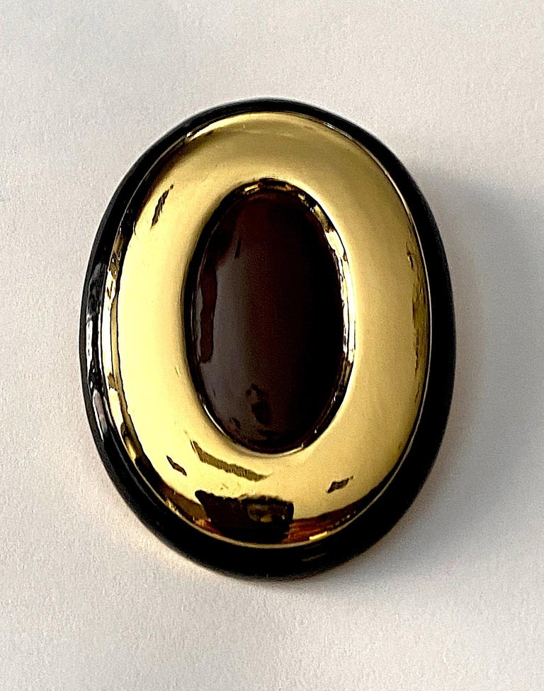 Made in Italy circa 1980 large oval button earrings. The earrings are gold plated with a milk chocolate enamel center and .25 of an inch black enamel border. Each clip back earring measures a large 1.75 inches wide, 2.38 inches tall and has a