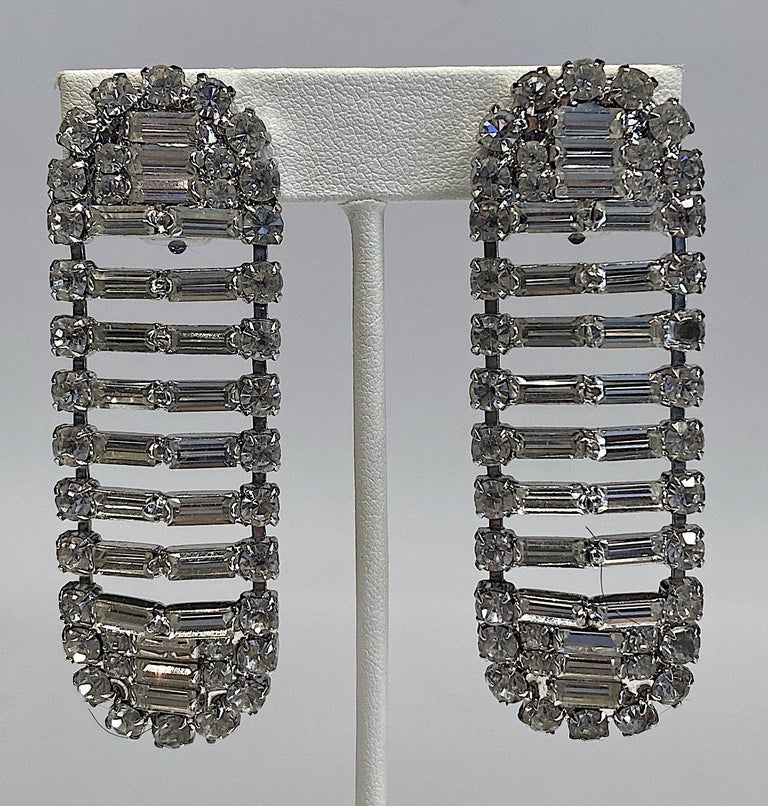 A sparkles and noticeable pair of Italian round and baguette rhinestone earrings from the 1980s. The earrings are large yet constructed with open spaces to keep them light and delicate in appearance. The metal is rhodium plated. Each earring has a