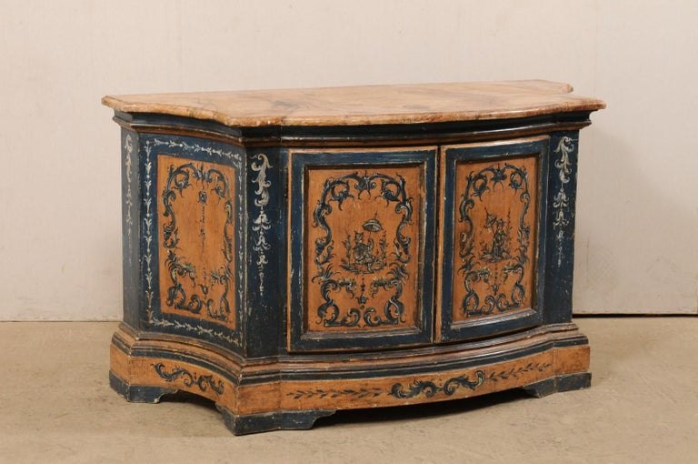 An Italian ornately painted wood console chest with faux-marble top from the 19th century. This antique buffet from Italy features a shapely front with bowed mid section flanked within curvy recessed sides, with a slightly overhanging top which
