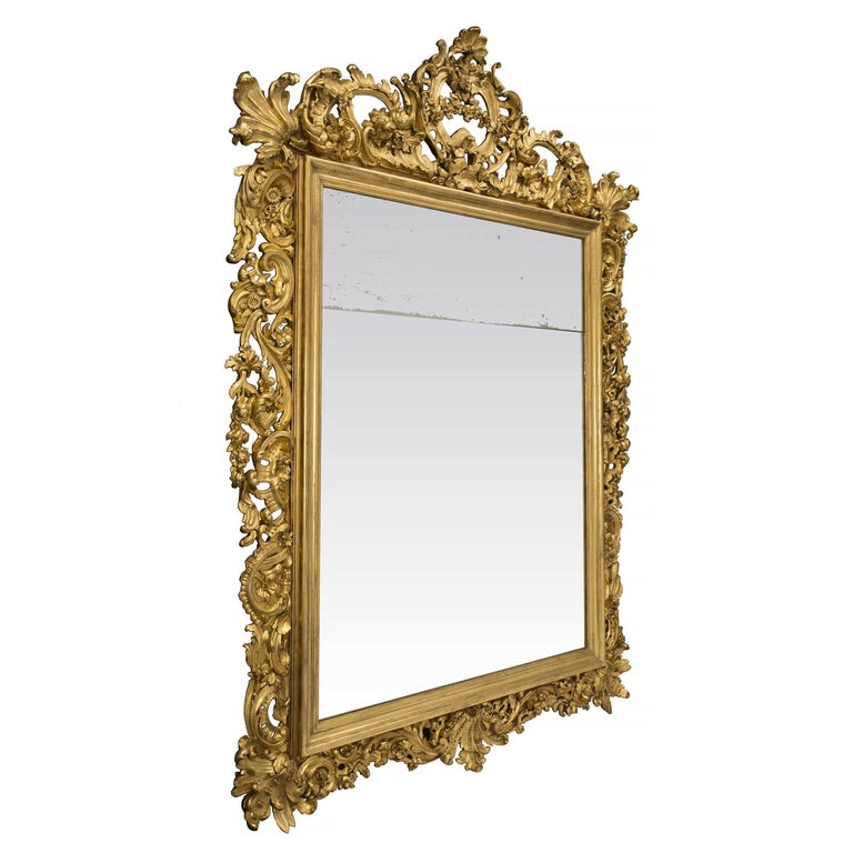 A most impressive and large scale Italian 19th century Baroque style giltwood mirror. The original rectangular mirror plate is framed within a fine mottled giltwood border. Extending throughout the frame are sensational and richly detailed carvings
