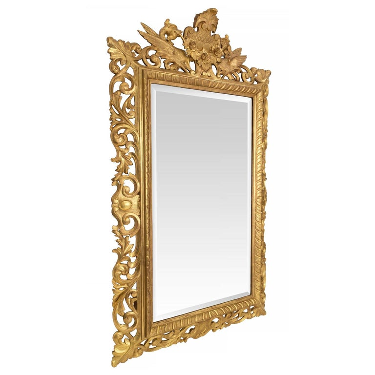 An outstanding Italian 19th century Baroque style giltwood mirror. The original beveled mirror plate is framed within a most decorative fluted pattern. Extending along the base and up each side are richly carved intricate pierced scrolled movements