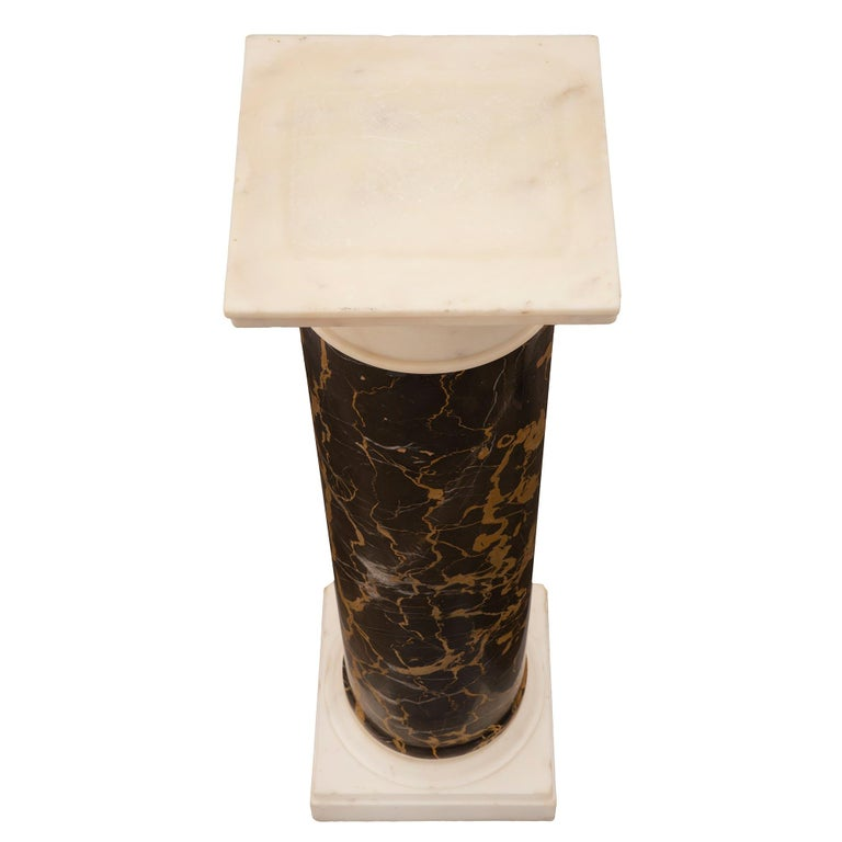 An impressive Italian 19th century neoclassical style white Carrara and Portoro marble pedestal column. The pedestal is raised by a square white Carrara marble base with a Fine mottled border below a circular mottled plinth. The circular central