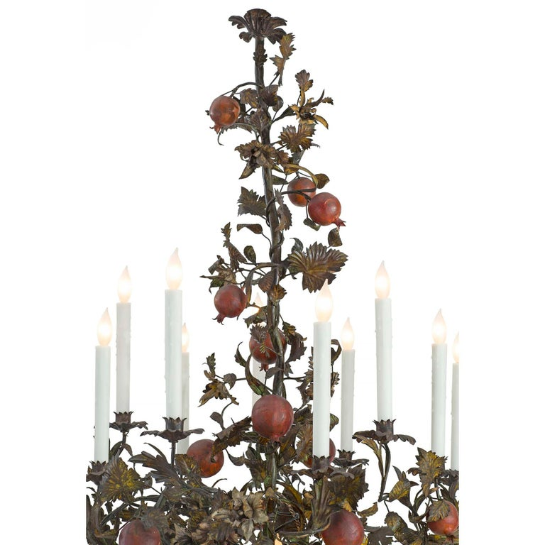 An extremely decorative and whimsical Italian 19th century patinated iron and pressed metal ten light chandelier. The chandelier with a central electrified weaved basket has ten scrolled foliate arms decorated by wonderfully colored pomegranates.