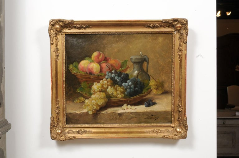 An Italian oil on canvas still-life painting from the 19th century in carved giltwood frame, signed Florentine. Created in Italy during the 19th century, this still-life painting depicts mouth-watering grapes and peaches displayed in two wicker