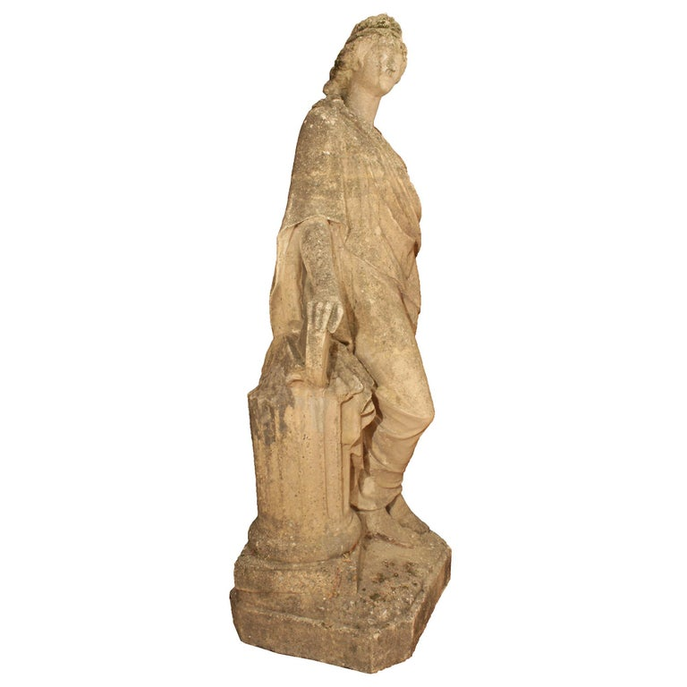 A lovely Italian 19th century stone statue. The Classic female figure is raised on a square stone base with cut corners. She is leaning on a fluted column with her legs crossed. The figural is adorned in classical dress with her hair up, dressed