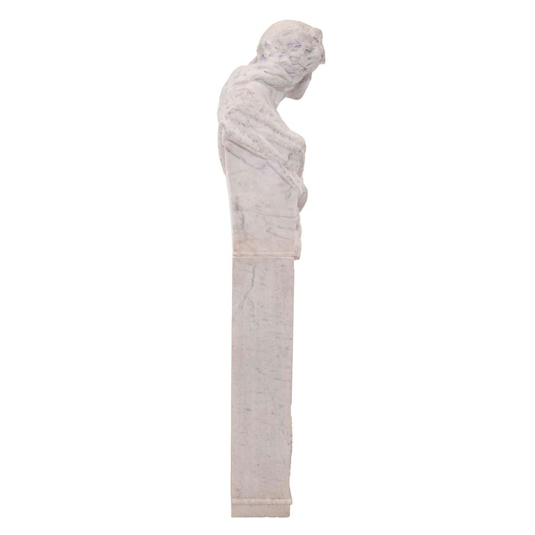 A very decorative Italian 19th century white Carrara marble freestanding statue of a Garden Maiden. The statue is raised by a rectangular marble pedestal with a richly carved floral wreath and a tied bow below a mottled raised panel. The upper
