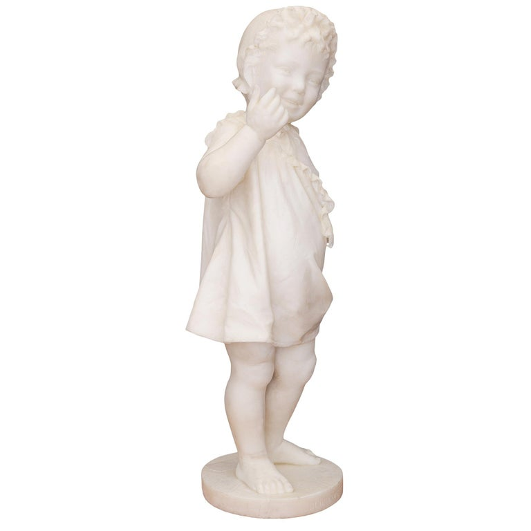 A most charming and wonderfully executed Italian 19th century white Carrara marble statue of a young girl, titled BUONANOTTE. The statue is raised by a circular base with a fine paver like design and the inscription BUONANOTTE at the front meaning
