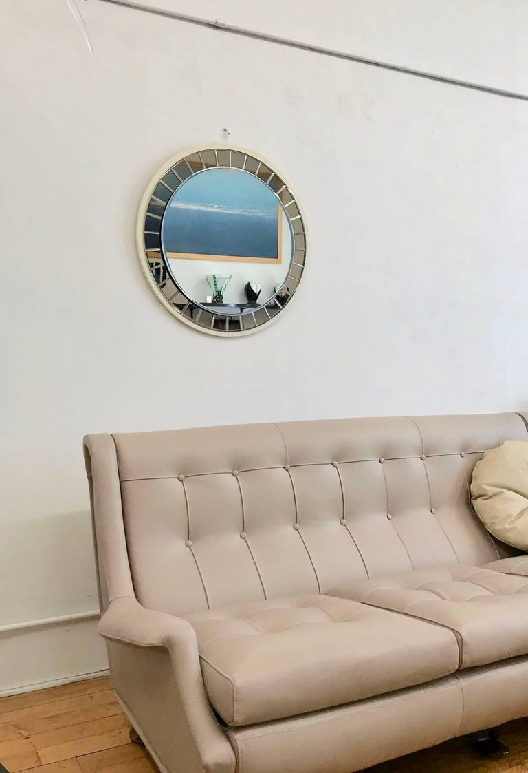 Italian 20th Century round mirror by Crystal Art with double layer of glass of different colors and a white lacquered wood back panel. The Mid-century mirror is in good condition while the wood back is in fair condition and presents some cracking