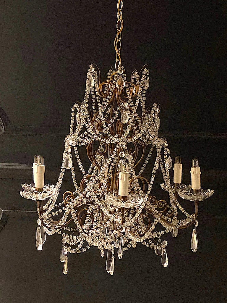 A charming Italian 1950s Hollywood Regency style gilt iron and glass bead and crystal chandelier. The body of the chandelier measures 24 inches in diameter and 24 inches high. There are six arms with candelabra sockets and scallop glass bobeches.