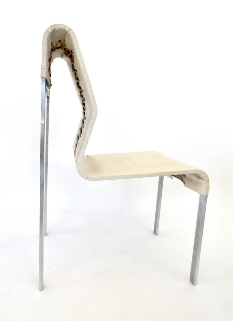 An Italian abstract strap steel and linen fabric side and statement chair.