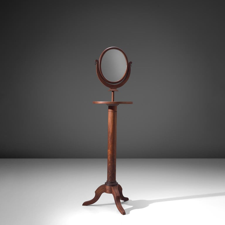 Mirror, walnut, glass, Italy, 1940s  This freestanding mirror is executed in walnut. It has an oval mirror, placed on a pedestal base with three legs. The height and angle of this mirror is easily adjustable to a height of 182 cm. It can be placed