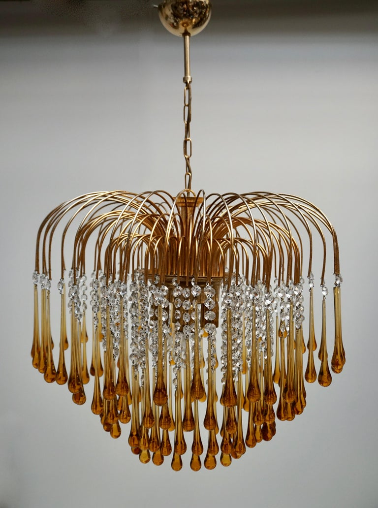 Elegant large brass and amber Murano crystal chandelier.   The lamp is decorated with hand blown amber crystal Murano teardrop glasses.   The chandelier emits a stunning light.   The lamp is fitted with four E27 light sockets. It comes with
