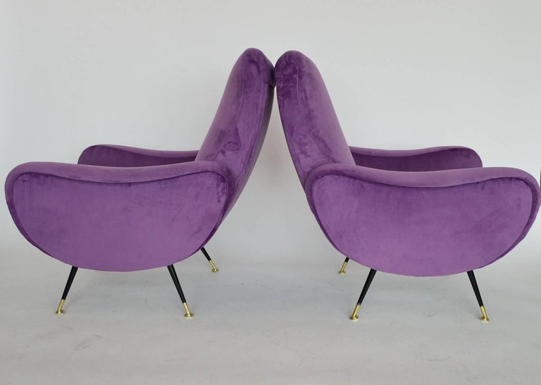 Amazing and comfortable pair of Italian original armchairs from the 1950s. Completely restored internally with quality material and outside reupholstered with light violet (or lilac) soft Italian velvet. The stiletto feet are original with brass