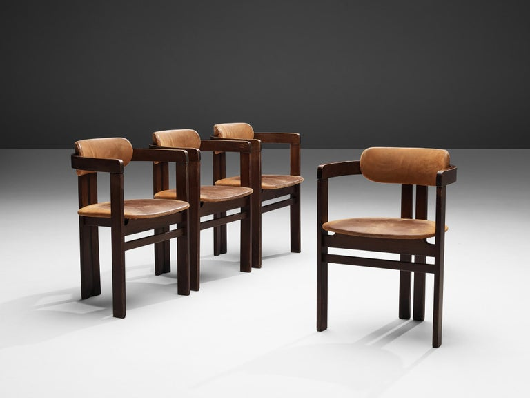 Armchairs, leather, lacquered wood, Italy, 1960s  Armchairs in wood with cognac leather. The chairs have a characteristic design, clearly inspired by the Pamplona chair of Augusto Savini. The chairs are functional and straightforward, yet very