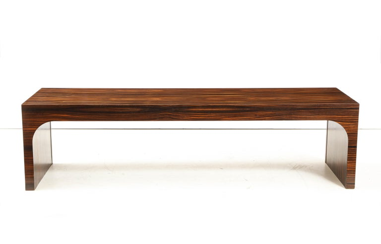 Italian Art Deco Macassar ebony waterfall shaped coffee table or bench. This exotic and very elegant wood was popular in the Art Deco modernist period for its lushness and striking coloration and depth. A stunning and sleek piece. Italy, circa