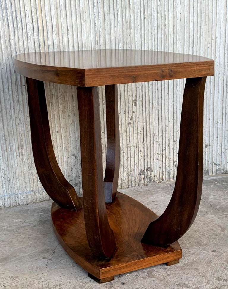 Italian Art Deco rectangular, oval side table, circa 1930s. Narrow ebonized feet and round finial at center base set off the figured walnut. Lower smaller round tier. Unknown maker.