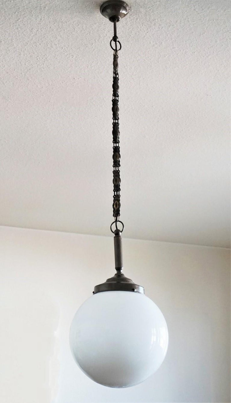 A large Italian ball hand blown opaline glass ball pendant with burnished brass mounts, chain and canopy, circa 1930-1939. One brass and porcelain Edison E27 light socket for a large sized light bulb up to 100W. Measures: Diameter 14