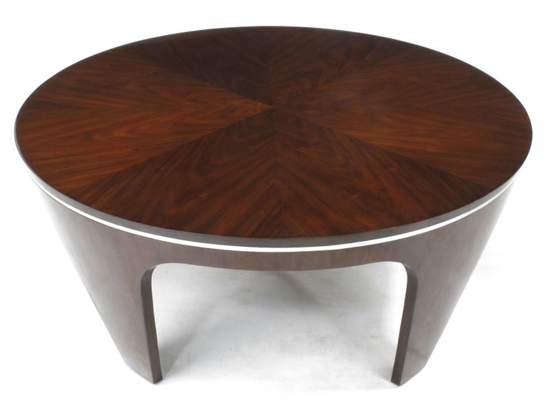 Art Deco inspired high gloss mahogany coffee table with chrome banding accent and parquetry top. Most likely of Italian origin, the sculptural legs are tapered inward creating a striking Silhouette. Comes with a protective glass top to keep the