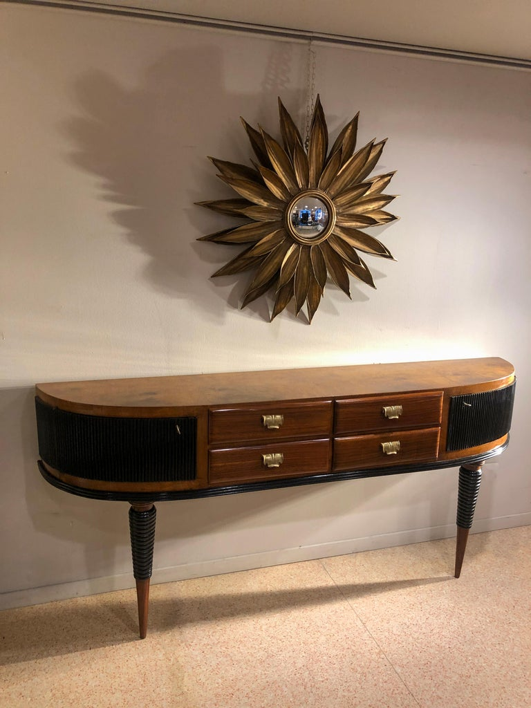 Art Deco rosewood table console credenza with rounded edges doors and four drawers with brass leaves shapes handles. There are some black lacquered ebonized parts such us the legs and the curved doors. The console measures D 38 cm, L 200 cm, H 90