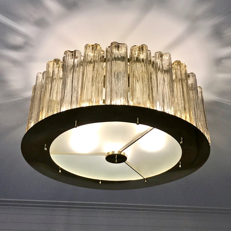A contemporary Italian bespoke modern chandelier, entirely handcrafted in Italy, customizable as flushmounts or pendants with different colors and finishes, here with a brass structure in a geometric circular shape, highlighted and made precious by