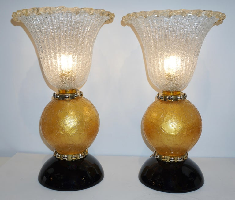 These lamps with Art Deco Design and Hollywood Regency flair are an exclusive vintage creation of the 1970s. The organic rounded design is enhanced by details of high quality craftsmanship: the bodies consist of crystal clear overlaid Murano glass