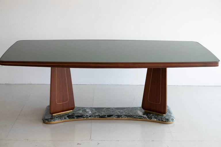 Gorgeous one of a kind Italian table with pedestal legs, marble base, brass inlayed mahogany with original green glass top. Would be an incredible power desk - or used as beautiful centre table.