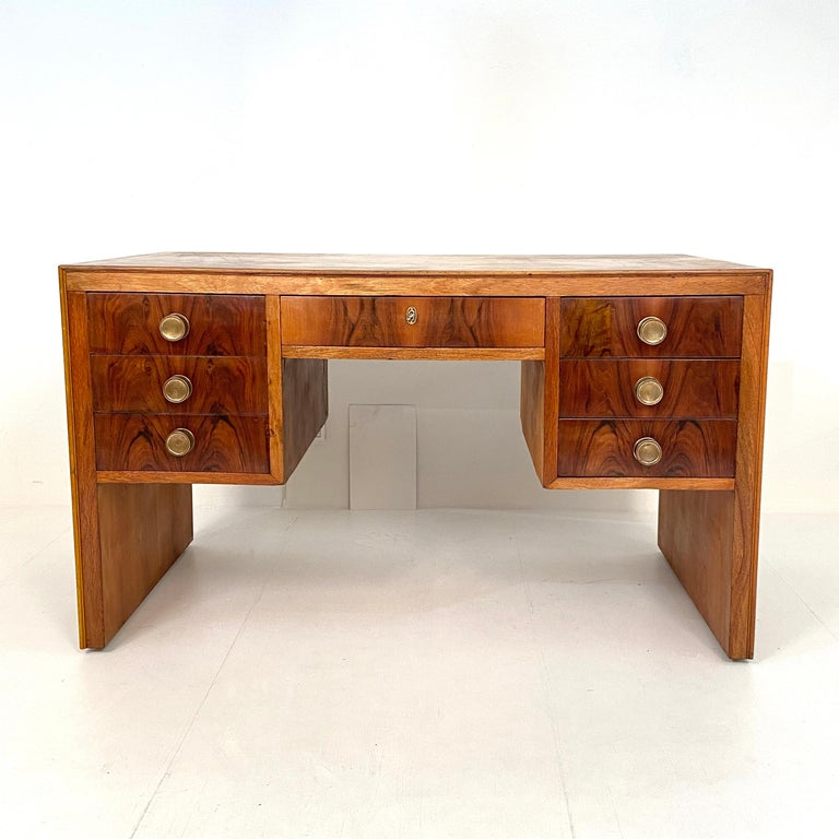 This Italian Art Deco writing desk was made circa 1930. It is out of beautiful light brown walnut, linoleum and has got brass handles. The drawer in the middle can be locked. It has got a beautiful patina. A unique piece which is a great